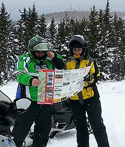 Snowmobilers with a trail map